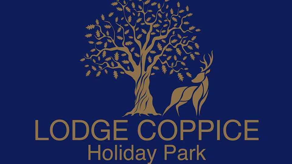 This is the Lodge Coppice logo, it has gold lettering and line drawn image on a dark blue background, the image is a tree with a deer below. The lettering reads, Lodge Coppice Holiday Park.