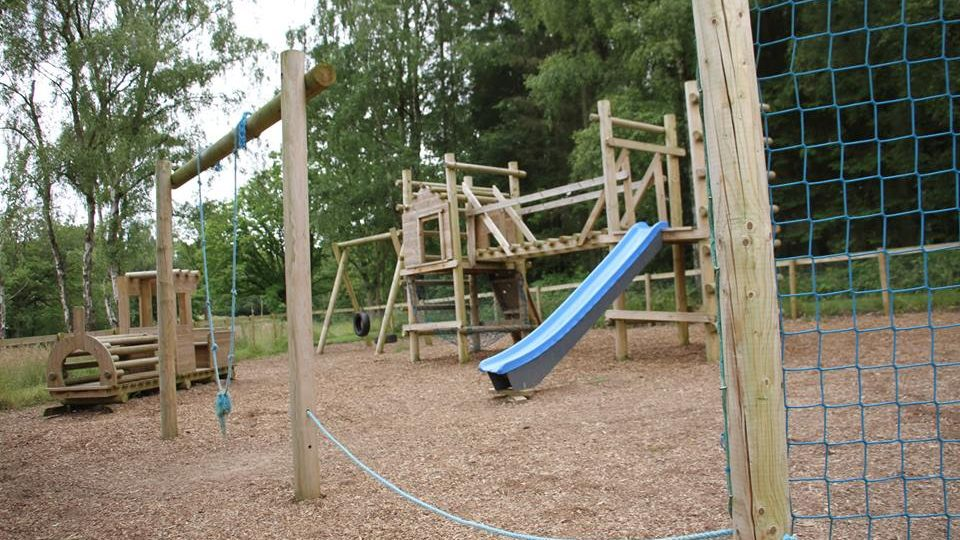 A soft barked playground with a selection of rustic wooden children's claiming frames, a slide, a rope climbing net and a swing.