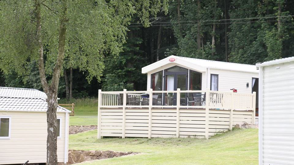 A cream coloured Carnaby static caravan, with French doors opening onto a decked area, with a outdoor furniture, backing onto the Wyre Forest.