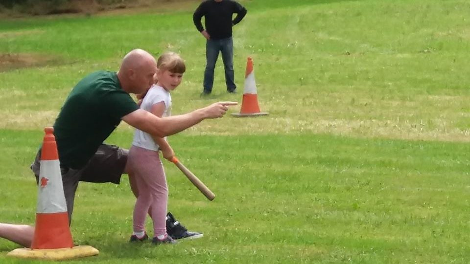 Traffic cones used to make the bases for a rounder's pitch, a man is speaking and pointing to a child who holds a rounder's bat.