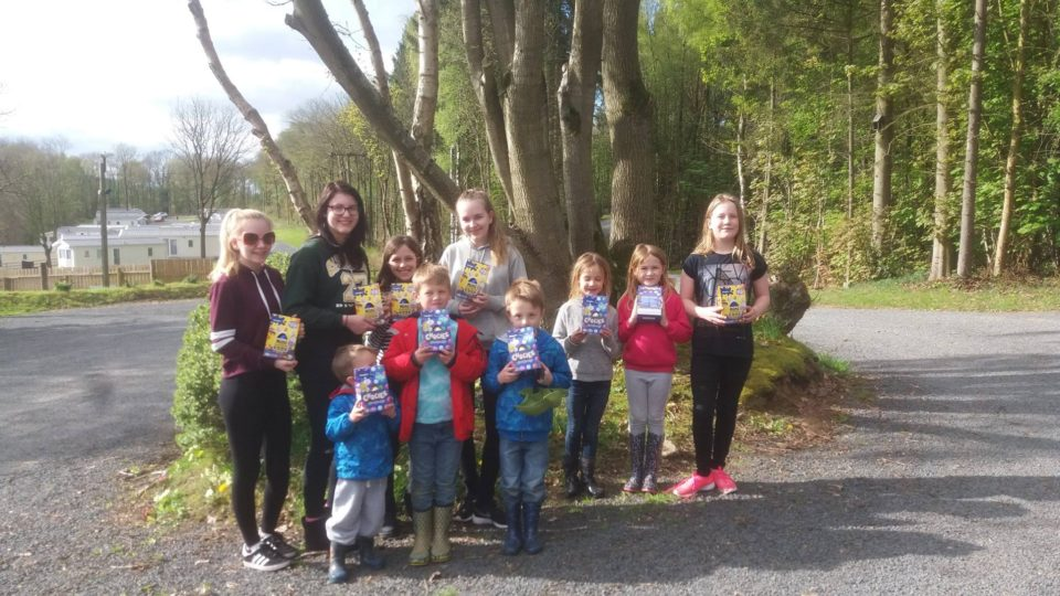 The Easter egg hunt winners show their winning eggs. Lodge coppice Caravan Park stretches away behind them surrounded by the Wyre Forest.