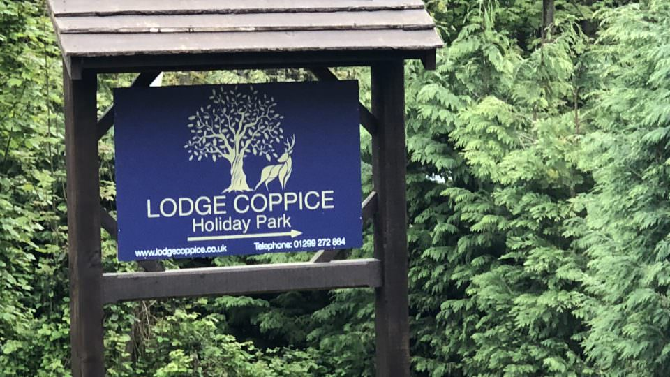 The roadside Lodge Coppice entrance sign has gold lettering on a blue background. There is a small slate roof above the sign and a green hedge behind.