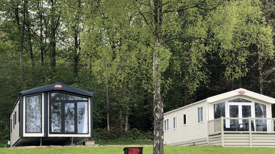 Two new static caravans at Lodge Coppice on the Wyre Forests edge. One caravan has a decked area to the front with a small picket fence.