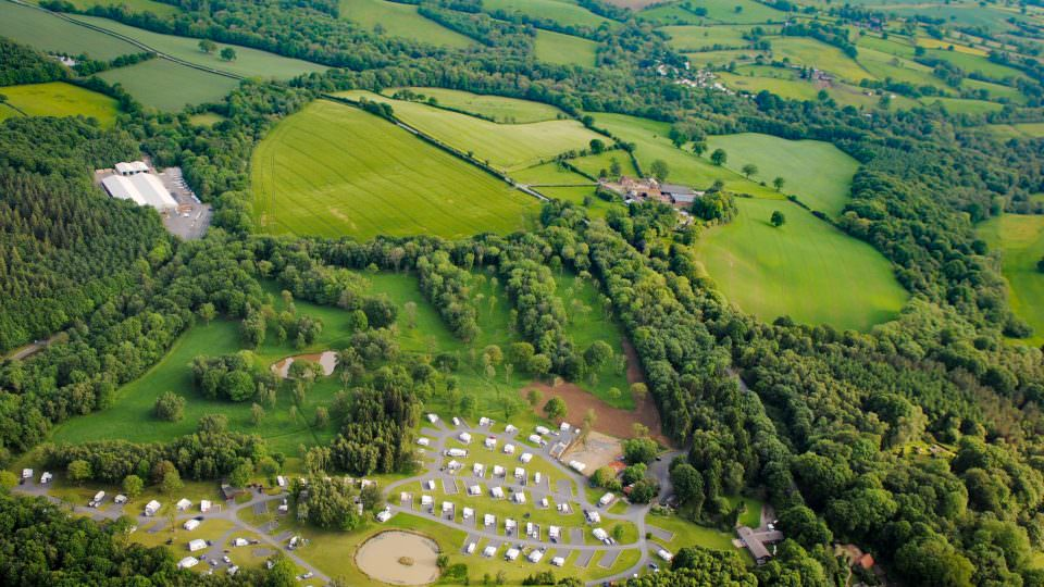 An aerial view of Lodge Coppice, the Park from above, lots of well spaced static caravan roofs, separated by mown grass, the Wyre Forest, fields of open countryside abound.