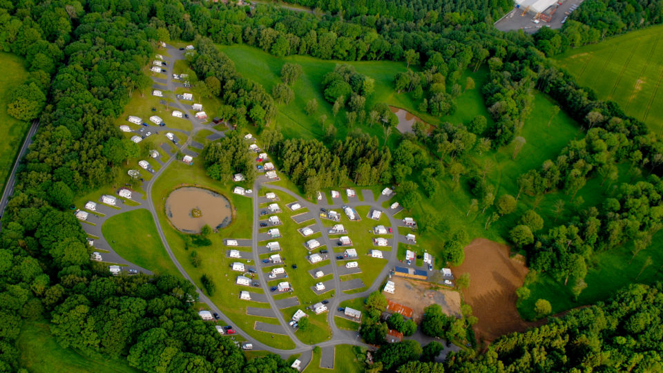 An aerial photograph of Lodge Coppice. Well spaced caravans, trees and the pool all seen from above.