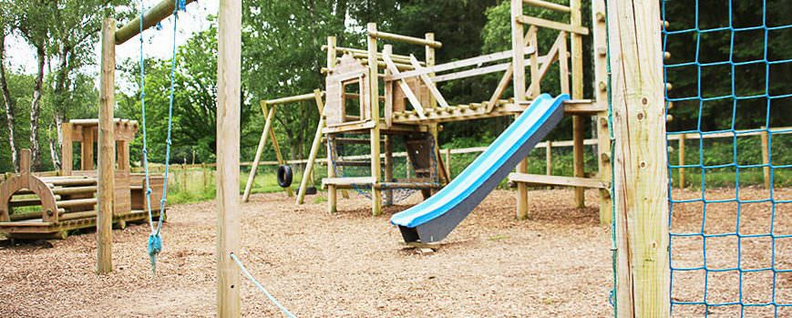 The Lodge Coppice playground set on soft bark with rustic climbing frames, rope nets, swinging tyres and bridges.