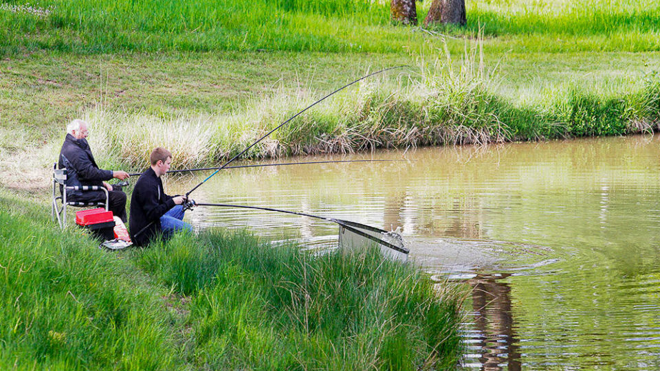 The Lodge Coppice pool with people fishing. A boy extends the landing net as it appears a fish may be on the line.
