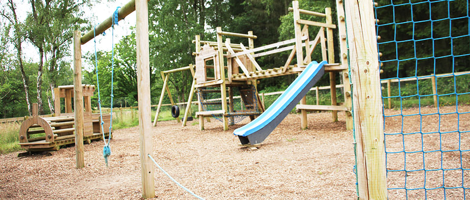 Lodge Coppice's rustic children's playground, there are log climbs; swings rope bridges and a blue slide. The ground is covered in bark for a soft landing.