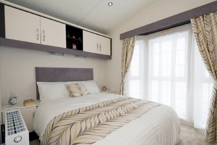 A static caravan's double bedroom, there are cupboards above the bed and a big window behind. The bed is made with attractive modern bed linen.
