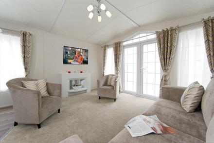 Beige carpets, matching comfy furniture, white walls, white ceiling and classy full length brown drapes compliment this open plan lounge. The room is flooded with light from the full glass French doors to the right. It's amazing it's a static caravan not a luxury villa!!
