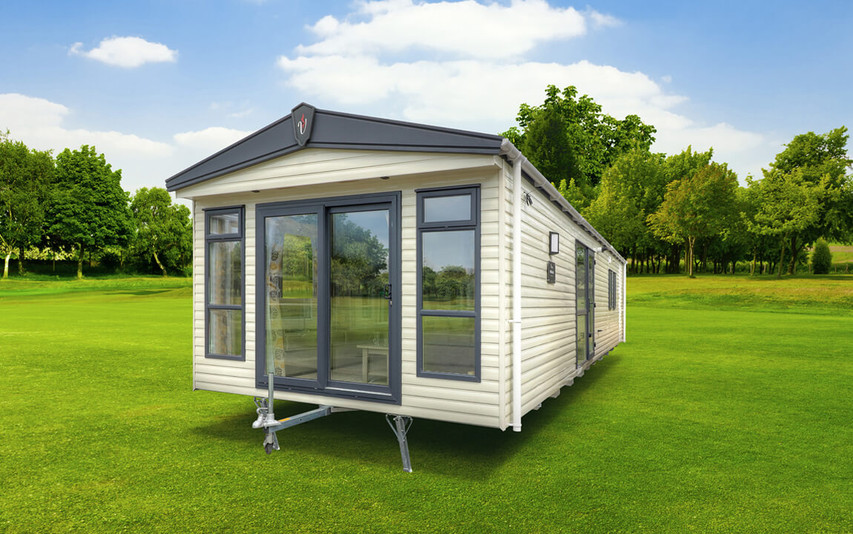 The end view of a brand new static caravan, it's positioned on mowed grass. It is cream with grey trims. The tow bar is showing indicating it's going to be moved.