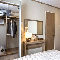 This bedroom storage is in a static caravan. Beyond the double bed are a door, a dressing table and wardrobe with clothes hanging. There is a dressing table, mirror and lamp.