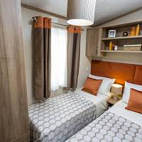 A static caravan's twin bedroom, two single beds, storage cupboards, a large window, the linen, curtains and cushions all match in beige, orange and cream.