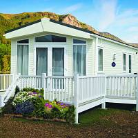 A static caravan with white railings, surrounding the decking