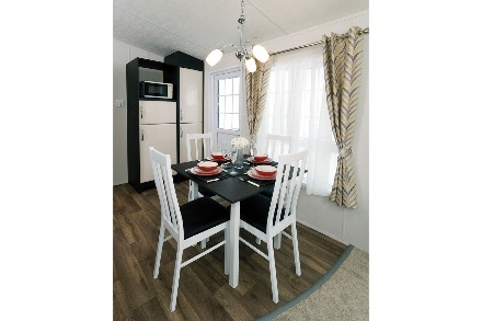 The dining area in a static caravan, the floor is laminate wood, the table and chairs are white, the table is laid for 4 people. There is a large window with curtains behind.