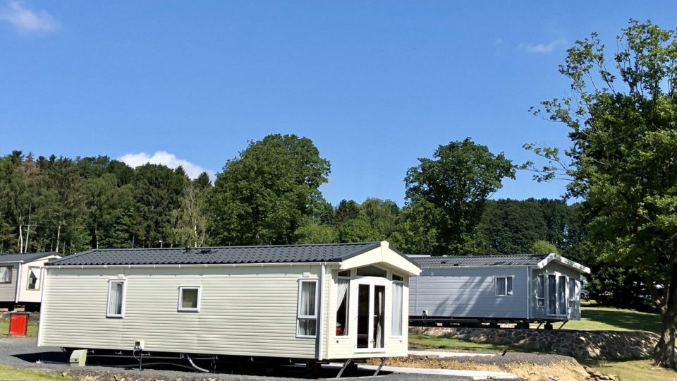 Two new static caravans are standing in front of the Wyre Forest. The shy is a perfect blue without a cloud in sight. The caravans are well spaced, slightly angled and gleaming in the sun light.