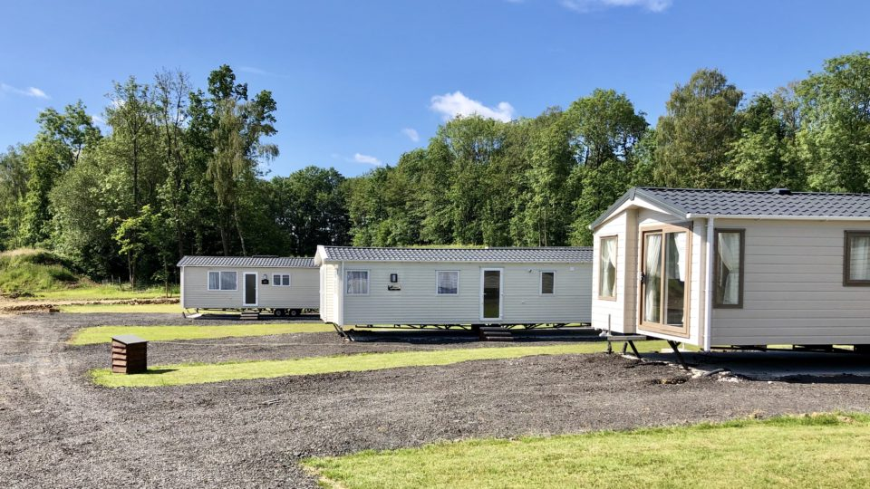 Three new static caravans, separated by well mowed grass inlets, there's a grey gravel road leading away and each caravan has its own private drive off. It's a beautiful day with hardly a cloud showing against the clear blue sky.