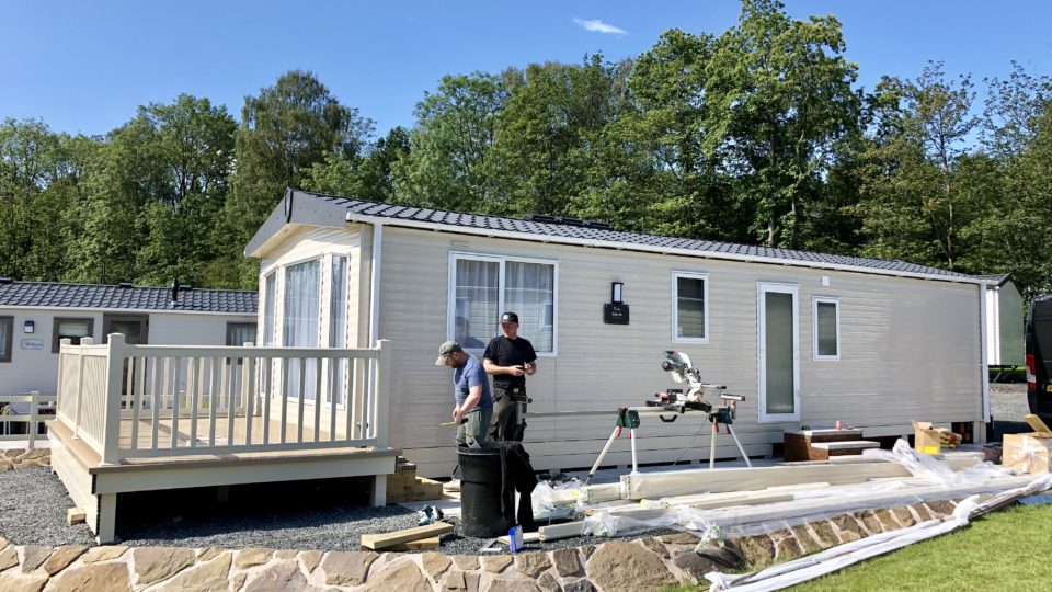 The Lodge Coppice team are finishing the decking around this new static caravan. This is a side view, the carpenter outside has an array of tools he is working with. This is another attractive position; it's elevated on a stone pad and is overlooked only by the tall trees of the Wyre Forest beyond.