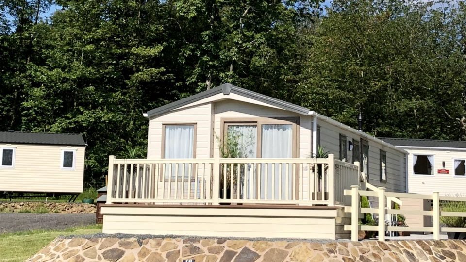 This new static caravan is elevated on a locally quarried tan and grey stone pad. It has decking and balustrade which is matching and looks stunning. This photo shows how well spaced the nearest other static caravans are and the cleaver planning that stops one static caravan overlooking another.