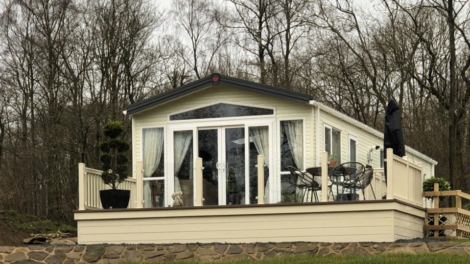 This new static caravan, on the edge of the Wyre forest, has a huge array of windows to the nose end and around the sides. It has tall trees behind and sits on the top of a grassey slope above the quiet fishing pool.