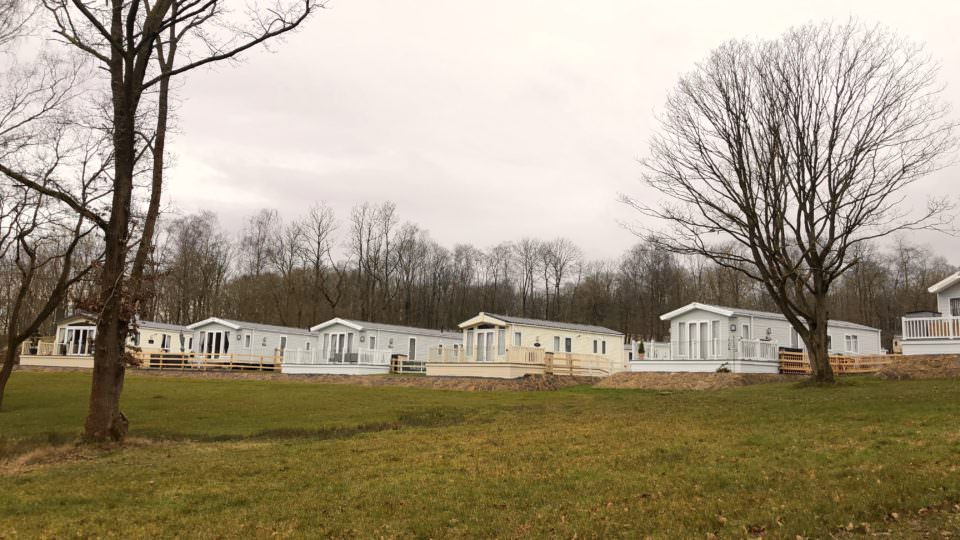 Five new welll spaced static caravans can be seen on a grassey slope in a clearing in the Wyre Forest.