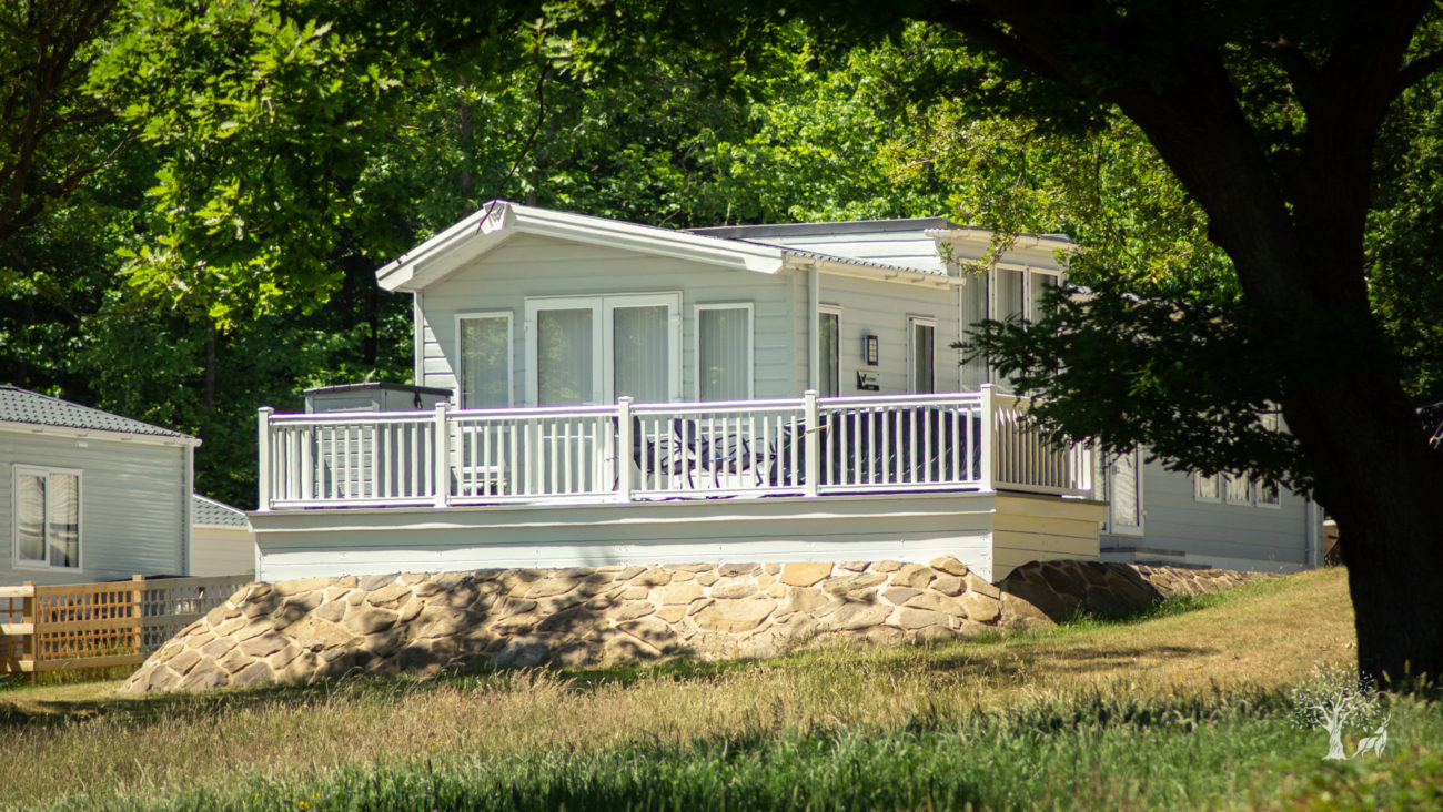 This is a fantastic individual static caravan; its contrasting white decking looks fabulous against the caravan's pale green shell. The van sits on one of our signature local stone pads and its private elevated position, flanked by tall trees makes it incredibly desirable.
