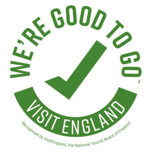 """The """"Visit England"""" logo. A green tick surrounded by the words """"We're good to go"""" which form a circle with the words """"Visit England"""" in reversed type."""