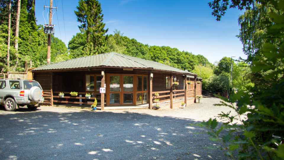 Our Site Wardens Lodge is timber clad, with a wide covered veranda. The area in front is gravel with parking for up to 12 vehicles. The sky is cloudless and the tall trees behind the lodge contrast beautifully, the rich greens against a solid blue sky.