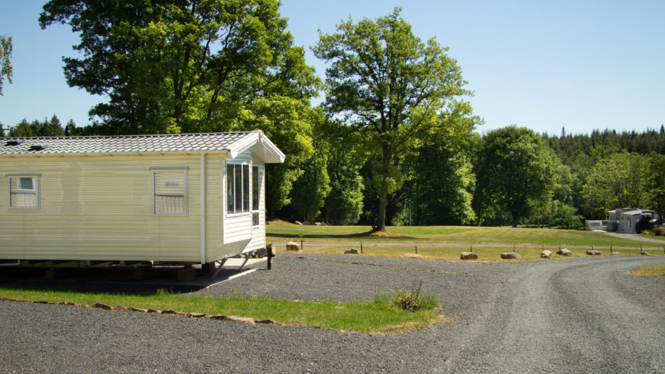 This shows the view past the end of a new static caravan, looking down into the forest in the distance. This photo shows how well spaced a new static at Lodge Coppice can be.