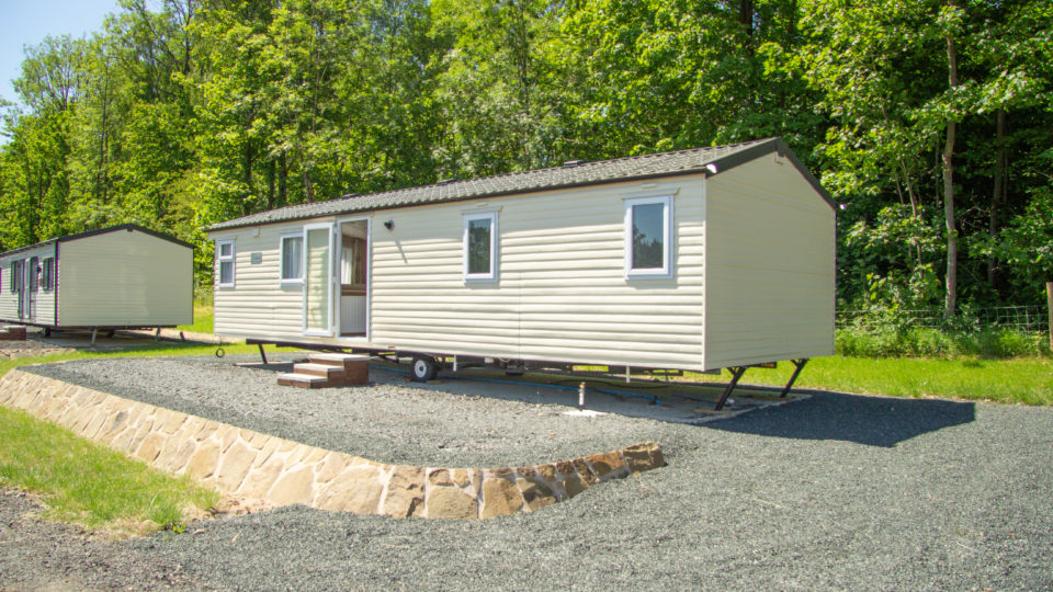 A new static caravan which has just arrived, temporary steps are position for access. There is no decking and the legs are visible and wound down.