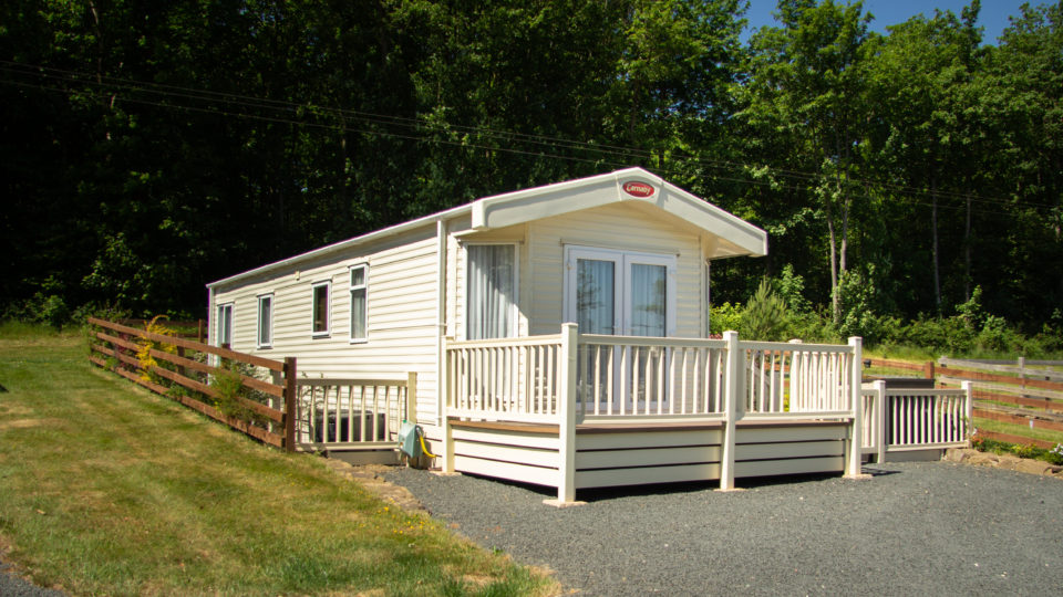 A well-spaced new cream Static caravan set against a backdrop of tall trees. Gravel drive infant and grass verge to left.