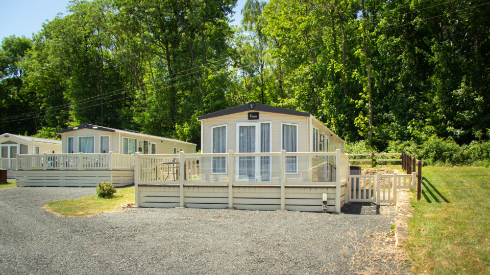 A wide new static caravan with a modern glass balustrade edging the front decking. This is a wide plot with tall trees and lawns to both sides and gravel parking front centre.