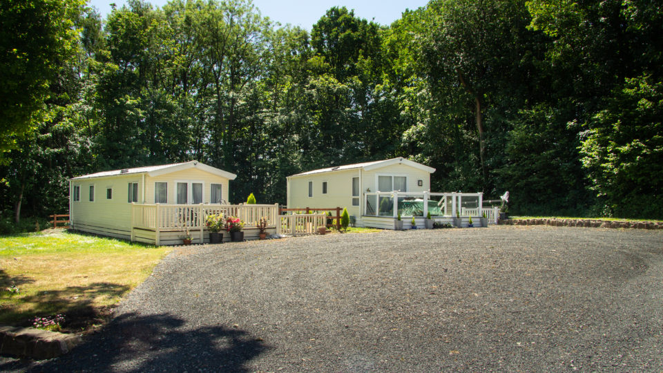 Two new static caravans are positioned with a large grey gravel area to the front making ample parking for several cars. the two plots are surrounded by tall trees.