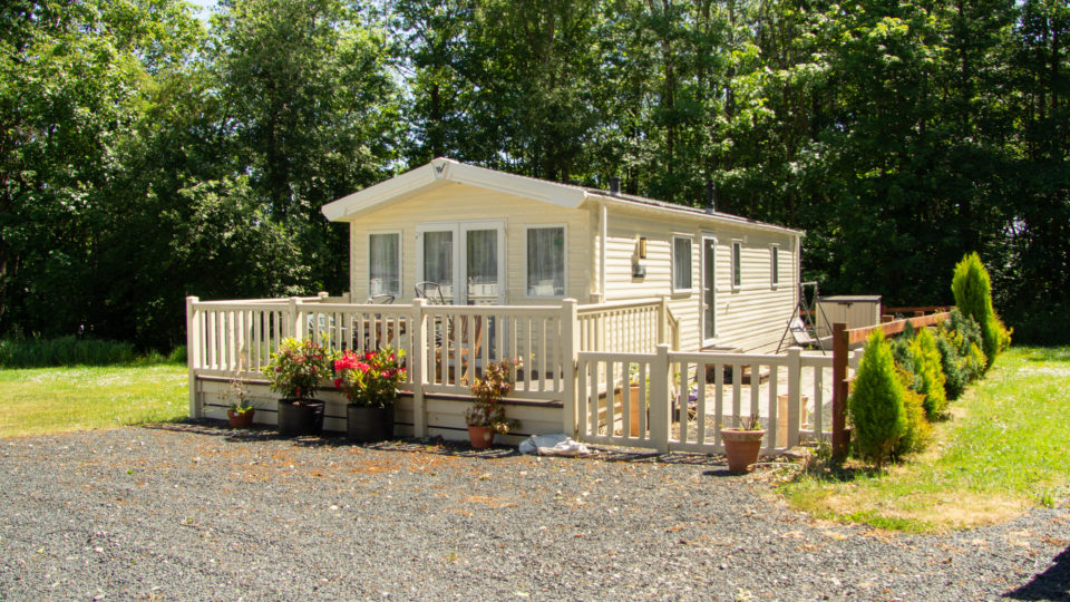 A beautiful holiday home, static caravan with matching cream decking and balustrade fencing surrounded by lots of flowering pot plants around the edge. Gravel parking in the fore ground and tall trees stretching into the blue sky.