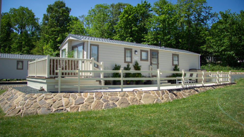A buff brown natural stone edged patio surrounds a new static caravan. This site has been built up so the caravan stands flat and level on it pad. The raised are has been fenced with cream post and rail style fencing. As ever at Lodge Coppice tall trees backdrop this photograph.