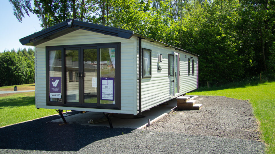 A new Willerby static caravan with distinctive dark grey contrasting windows against the light pastel cream body. The temporary steps are placed so people can see inside. This new static is positioned against a backdrop of tall trees and is surrounded by grey gravel.