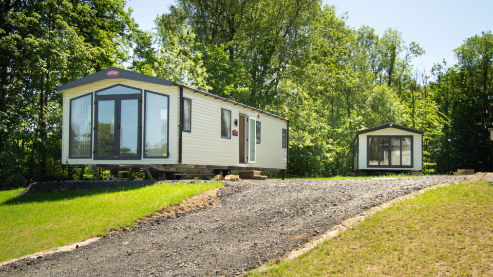 When positioning new static caravans, we try to step them forward and back, so views are less interrupted and living rooms don't overlook each other. This photo shows that in practice with cleverly staggering of one behind another at slightly different angles. There's a grey gravel drive between them allowing access and tall trees behind.