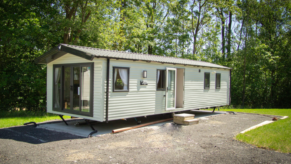 This brand-new static caravan is in brown and cream. It's just arrived. There are temporary steps in front of the side entrance, so customers can view inside and then if choosen see the available sites where we can site it for them. The decking style, material and colour can all be chosen at this point.
